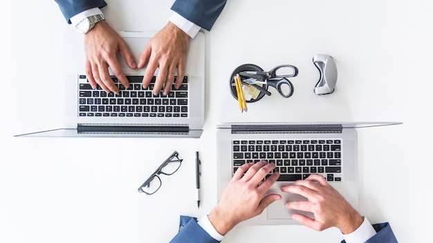 Eine obenliegende ansicht der hand des geschäftsmannes schreibend auf laptop über weißer tischplatte