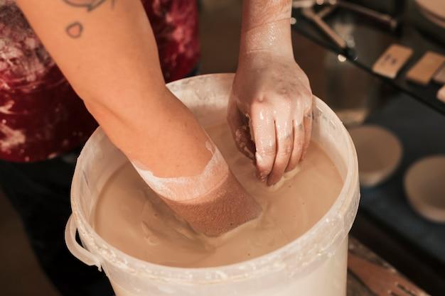 Eine obenliegende ansicht der hand des weiblichen töpfers die farbe mit der hand mischend