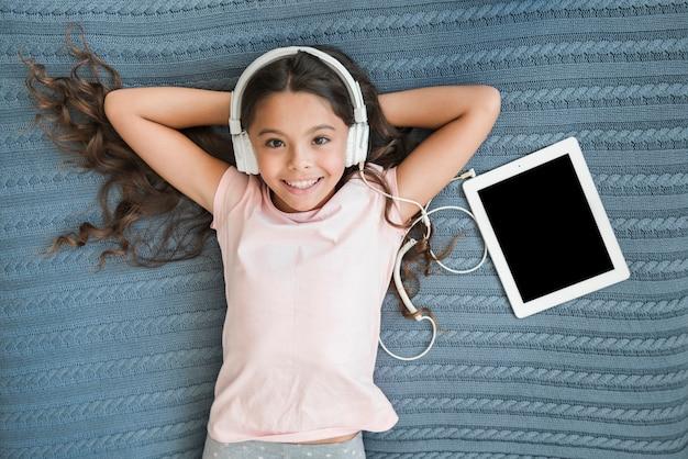 Eine obenliegende ansicht der hörenden musik des lächelnden mädchens auf dem kopfhörer befestigt an der digitalen tablette