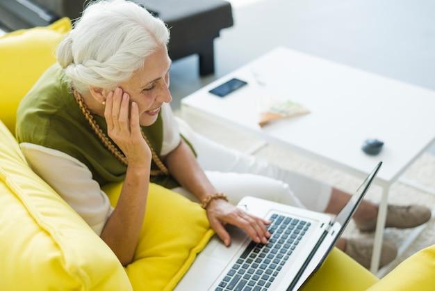 Eine obenliegende ansicht der lächelnden älteren frau, die laptop verwendet