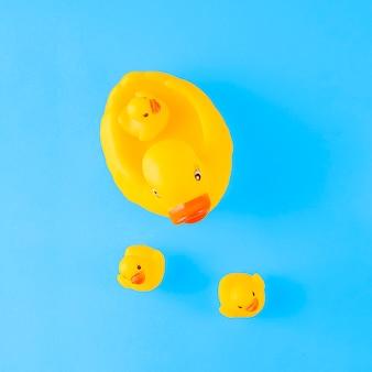 Eine obenliegende ansicht der netten gelben gummiente mit entlein gegen blauen hintergrund