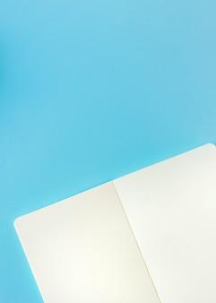 Eine obenliegende ansicht der offenen leerseite gegen blauen hintergrund