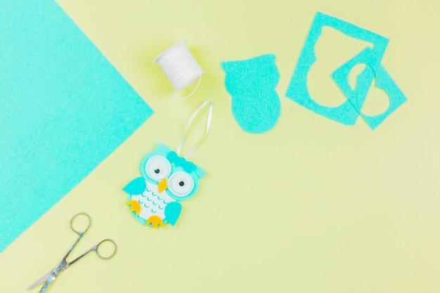 Eine obenliegende ansicht der papiereule mit threadspule und -schere auf gelbem hintergrund