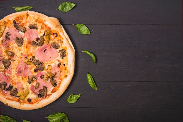 Eine obenliegende ansicht der selbst gemachten pizza, die mit basilikum verziert wird, verlässt auf hölzerner planke