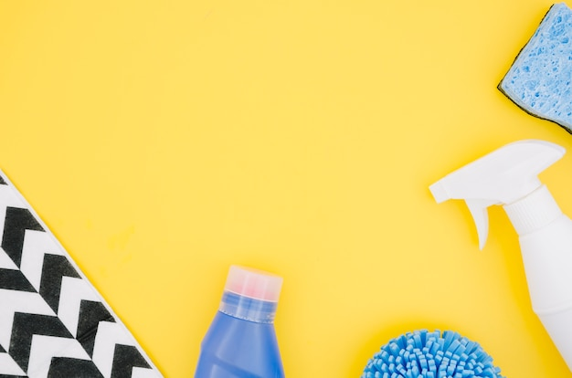 Eine obenliegende ansicht der sprühflasche und des schwammes auf gelbem hintergrund