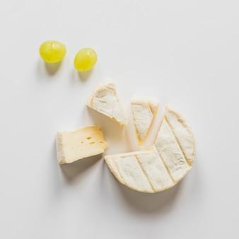 Eine obenliegende ansicht der trauben und der käseblöcke getrennt auf weißem hintergrund