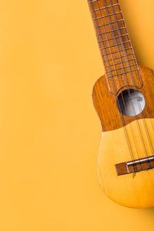 Eine obenliegende ansicht der ukulele auf gelbem hintergrund