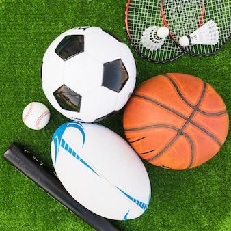 Eine obenliegende ansicht der unterschiedlichen art der sportausrüstung auf grünem rasen