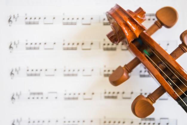 Eine obenliegende ansicht der violinenrolle und -schnüre auf musikalischen anmerkungen