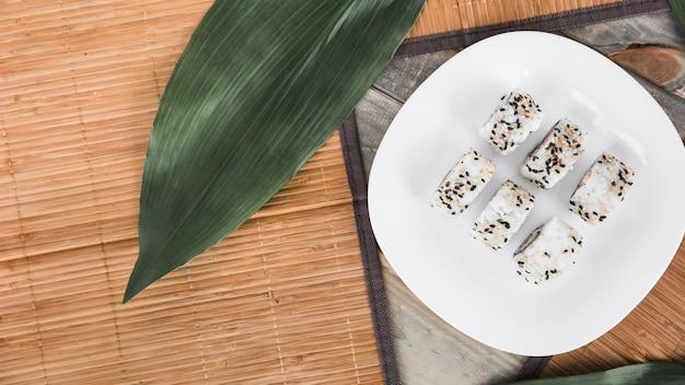 Eine obenliegende ansicht der weißen sushirolle in der platte mit grünen blättern und placemat
