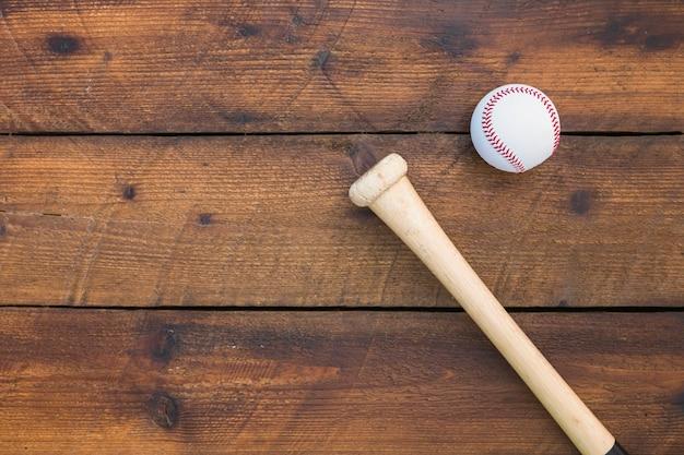 Eine obenliegende ansicht des baseballschlägers und des balls auf holztisch