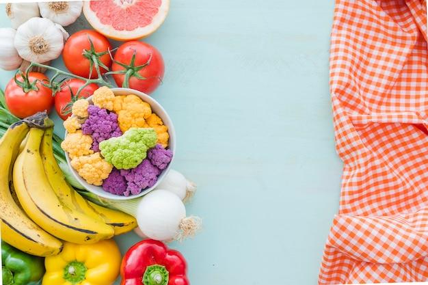Eine obenliegende ansicht des gesunden gemüses und der serviette über dem farbigen hintergrund