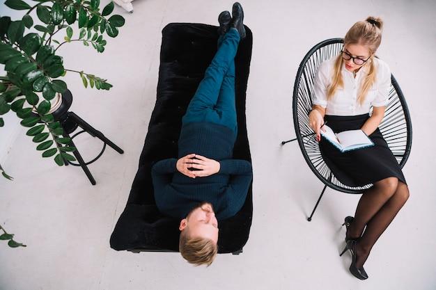 Eine obenliegende ansicht des jungen weiblichen psychologen, der jungen mann während der psychologischen therapiesitzung konsultiert