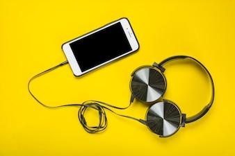 Eine obenliegende Ansicht des Kopfhörers befestigt mit Mobiltelefon auf gelbem Hintergrund