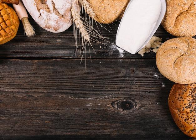 Eine obenliegende ansicht des mehls in der schaufel mit gebackenen broten auf tabelle