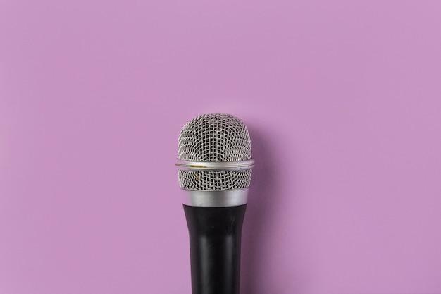 Eine obenliegende ansicht des mikrofons auf rosa hintergrund