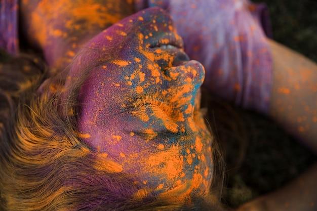 Eine obenliegende ansicht des orange holi farbpulvers auf dem gesicht der frau