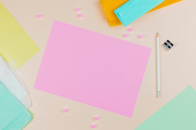 Eine obenliegende ansicht des rosa leeren papiers mit bleistift und bleistiftspitzer auf farbigem hintergrund