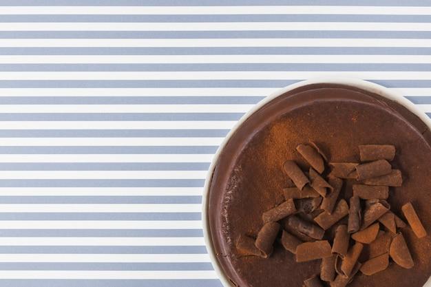 Eine obenliegende ansicht des schokoladenkuchens auf streifenhintergrund