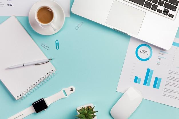 Eine obenliegende ansicht des schreibtischs mit briefpapier, laptop, maus und intelligenter uhr auf blauem hintergrund