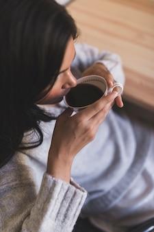 Eine obenliegende ansicht des trinkenden kaffees des mädchens