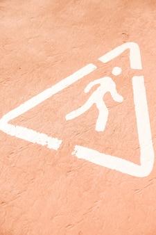 Eine obenliegende ansicht des warnzeichens der weiß gemalten fußgänger