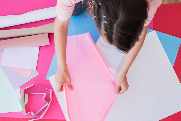 Eine obenliegende ansicht einer frau, die rosafarbenes kartenpapier anhält