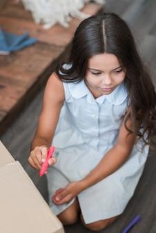 Eine obenliegende ansicht einer mädchenzeichnung mit filzstiftmarkierung auf pappschachtel