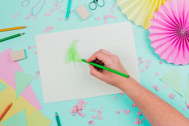Eine obenliegende ansicht einer person, die mit grünem bleistift auf weißbuch über dem knickentenhintergrund zeichnet