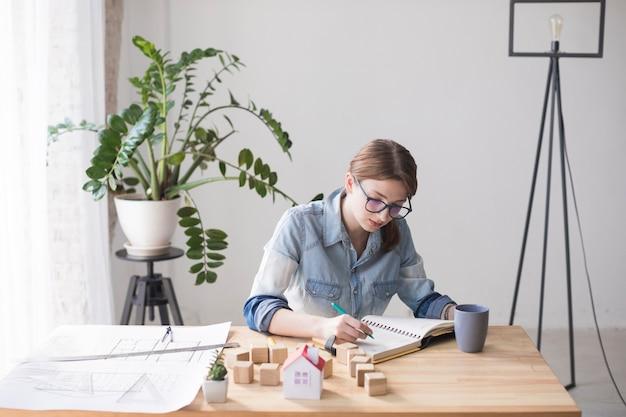 Eine obenliegende ansicht einer weiblichen immobilienagentur, die im büro arbeitet