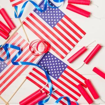 Eine obenliegende ansicht von amerikanischen flaggen mit bändern und kracher auf weißem schreibtisch