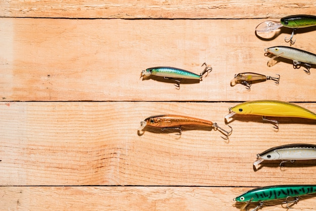 Eine obenliegende ansicht von bunten fischereiködern auf hölzernem schreibtisch