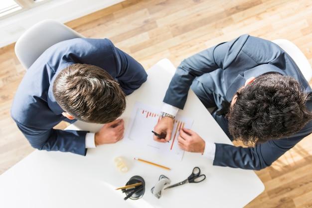 Eine obenliegende ansicht von den geschäftsmännern, die an unternehmensfinanzbericht über dem weißen schreibtisch arbeiten