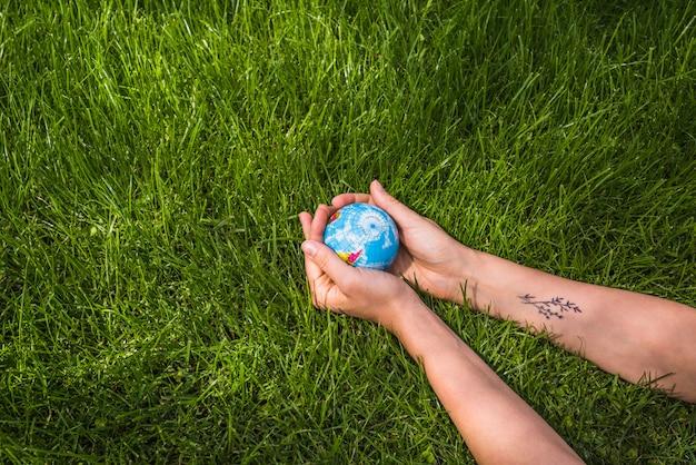 Eine obenliegende ansicht von den händen, die kugelball auf grünem gras halten