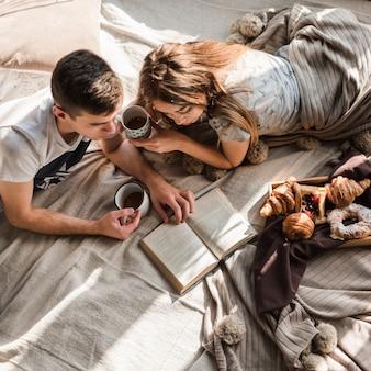 Eine obenliegende ansicht von den paaren, die auf dem bett hält tasse kaffee-lesebuch liegen