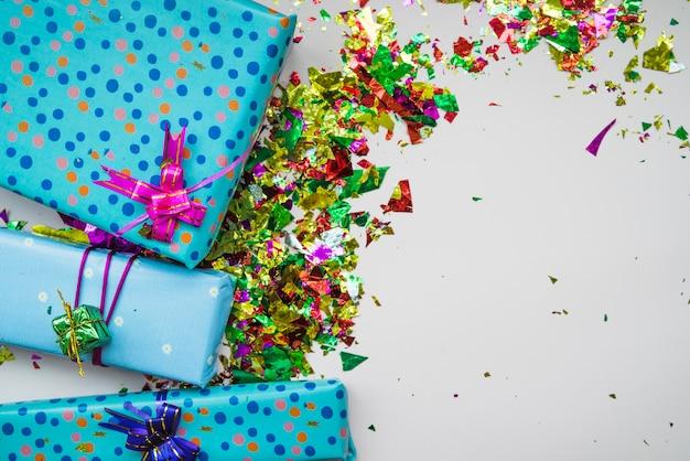 Eine obenliegende ansicht von eingewickelten geschenkboxen mit bunten konfettis auf grauem hintergrund