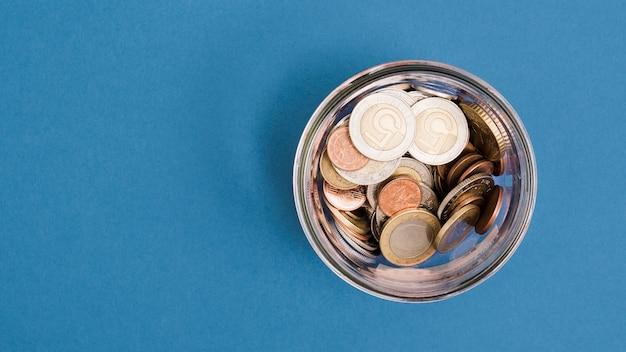 Eine obenliegende ansicht von münzen im glasgefäß auf blauem hintergrund