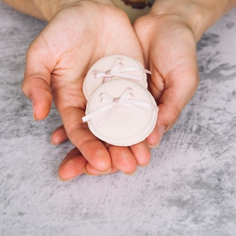 Eine obenliegende Ansicht von rosa Makronen mit Bogen in den Händen