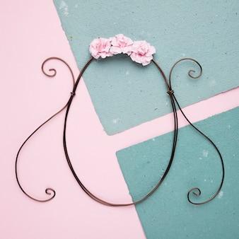 Eine obenliegende ansicht von rosa rosen über dem ovalen rahmen auf papier gegen rosa hintergrund