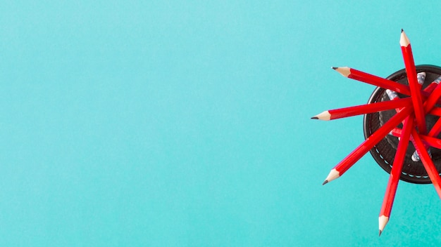 Eine obenliegende ansicht von roten bleistiften im halter gegen türkishintergrund