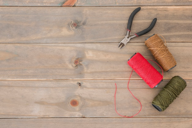 Eine obenliegende ansicht von zangen und von bunten garnspulen auf hölzernem schreibtisch