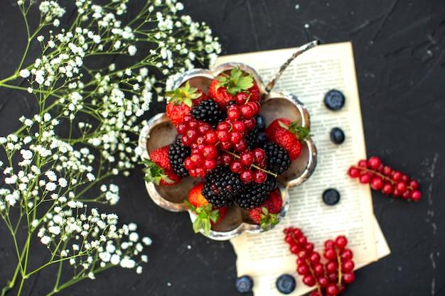 Eine obere nahaufnahme sehen frische früchte bunte beeren um papier und weiße blumen auf der dunklen oberfläche