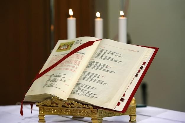 Eine offene bibel und drei kerzen dahinter