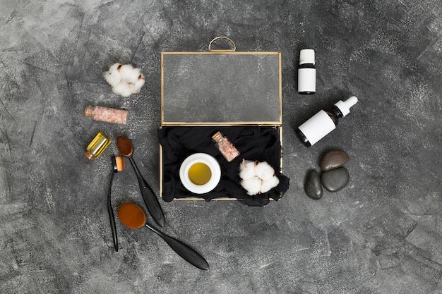Eine offene kiste mit honig; rosa himalayasalz und baumwollknospe mit kosmetikprodukten auf konkretem schwarzem hintergrund