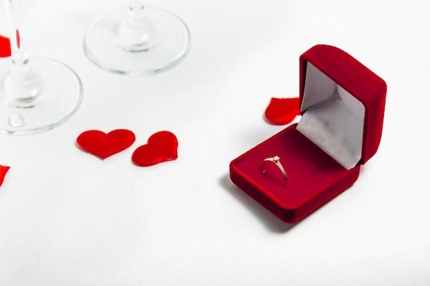 Eine offene rote schachtel mit einem ring für einen heiratsantrag neben gläsern champagner und konfetti aus herzen. draufsicht.