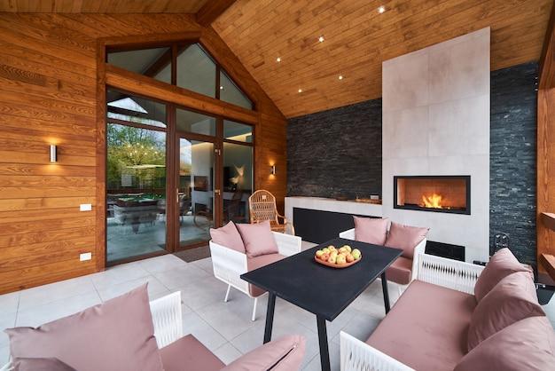 Eine offene terrasse mit tisch, stühlen, kamin und äpfeln. niemand.