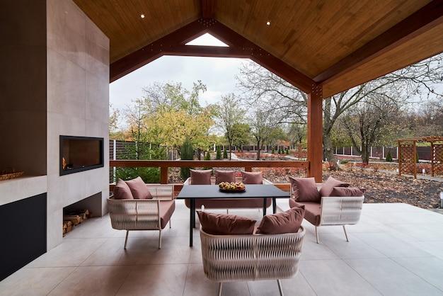 Eine offene terrasse mit tisch, stühlen, kamin und äpfeln.