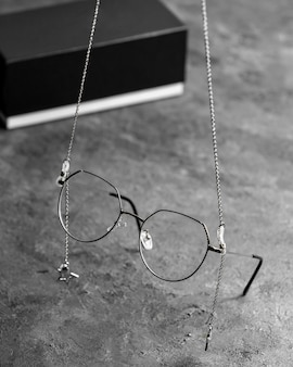 Eine optische sonnenbrille mit vorderansicht auf dem grauen schreibtisch mit silbernen ketten isolierte sichtsichtaugen