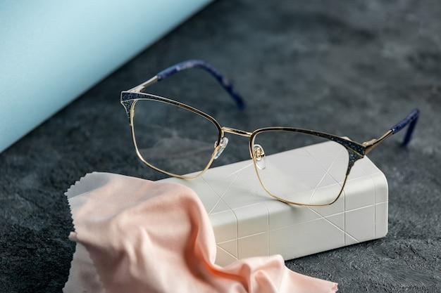 Eine optische sonnenbrille mit vorderansicht auf dem grauen schreibtisch zusammen mit cremefarbenem reinigungsgewebe isolierte die sichtsichtaugen