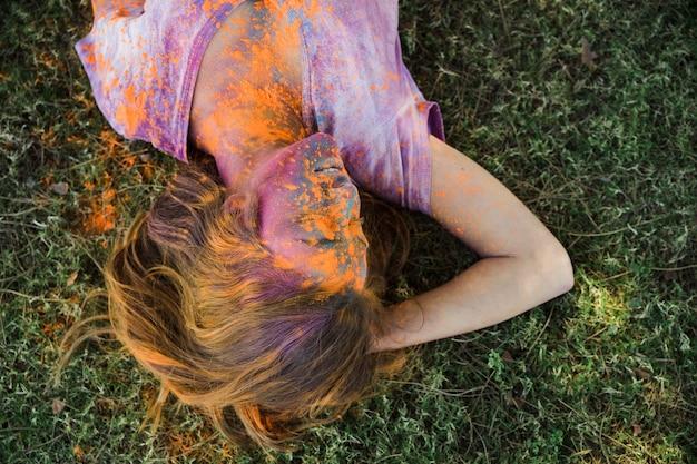 Eine orange holi farbe auf dem gesicht der frau, das auf grünem gras liegt